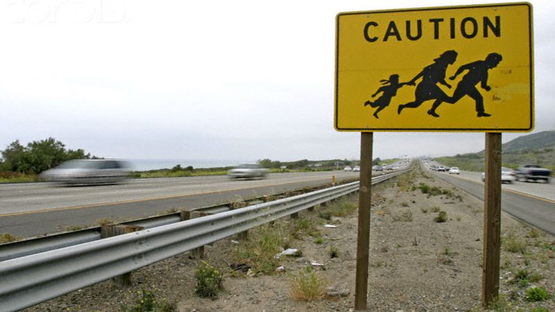 16 Apr 2004, San Diego, California, USA --- A San Diego, California sign warns drivers of Mexicans darting across the freeway to freedom. --- Image by © Mark Allen Johnson/ZUMA/Corbis